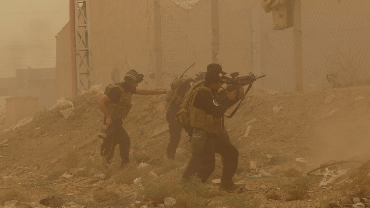 Security forces defend their headquarters against attacks by Islamic State extremists during sand storm in the eastern part o