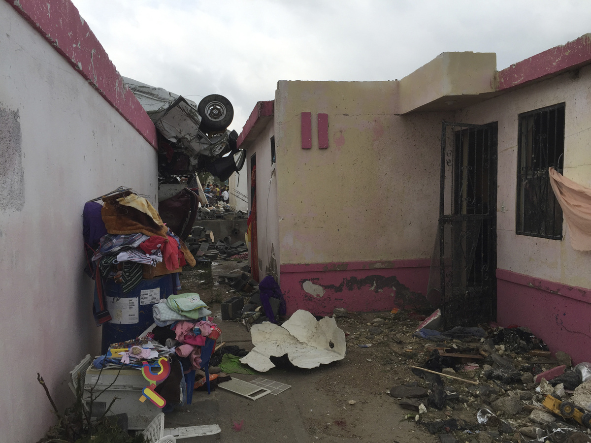 A vehicle lies on the rooftop of a home after a powerful tornado swept past in Ciudad Acuna, northern Mexico, Monday, May 25,
