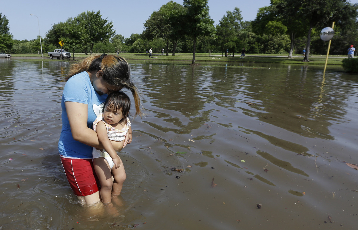 Gabby Aviles carries her daughter Audrey through floodwaters outside their apartment in Houston, Tuesday, May 26, 2015. Heavy