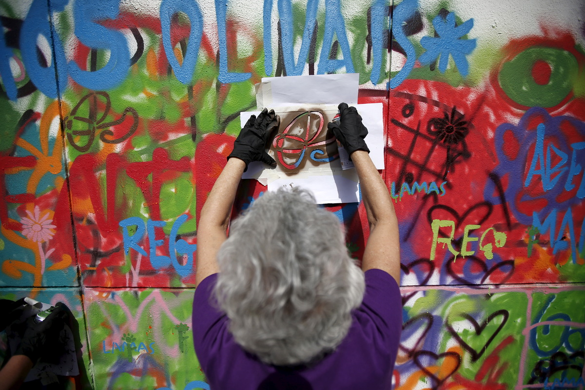 A woman sprays her design on a wall during a graffiti class offered by the LATA 65 organization in Lisbon, Portugal May 14, 2