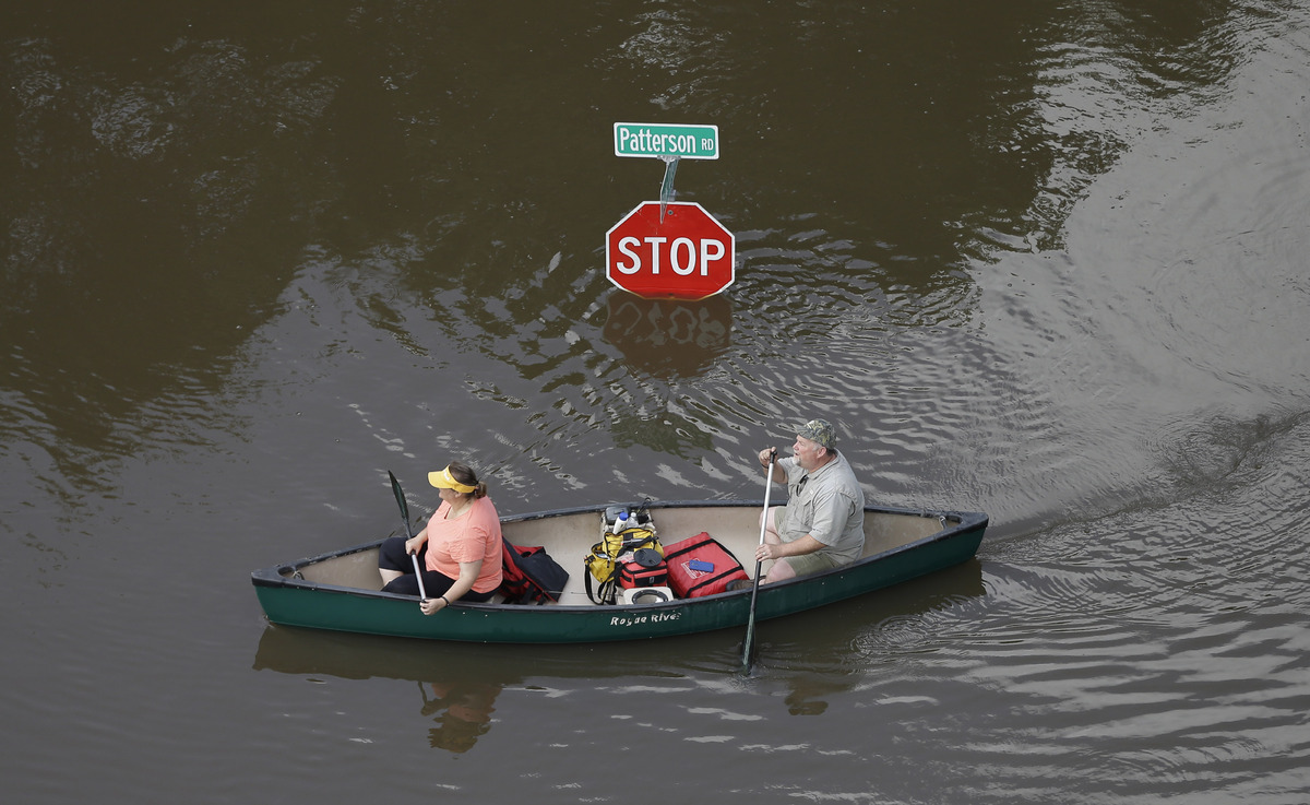 In this aerial photo, people canoe through floodwaters past a stop sign near Bear Creek Park Saturday, May 30, 2015, in Houst