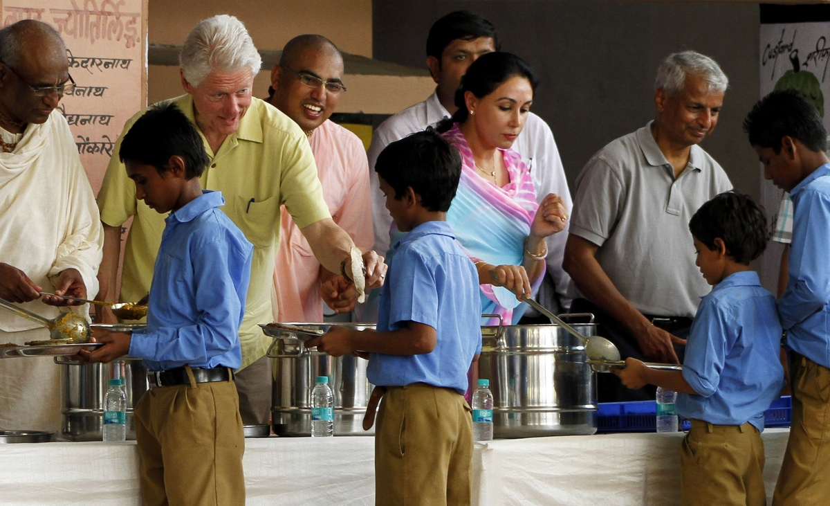 Former U.S. President Bill Clinton, second left, serves food to a schoolboy at a kitchen run by Akshaya Patra Foundation, a n