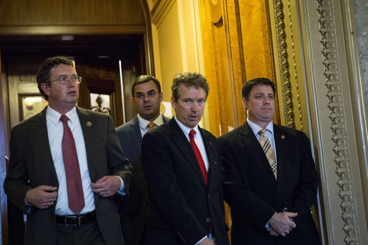 Rep. Thomas Massie (R-Ky.), left, and Sen. Rand Paul (R-Ky.), center, exit the Senate floor after Paul spoke about surveillan