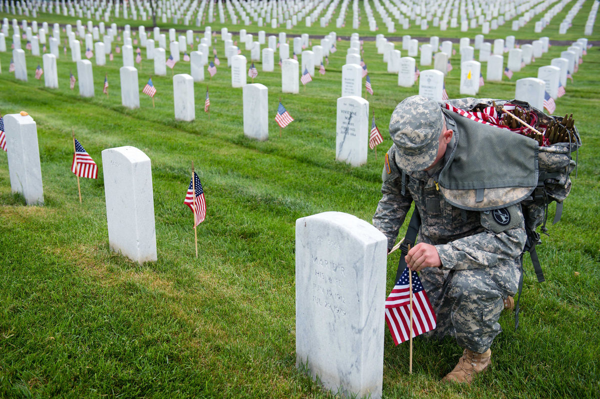 A U.S. Army 3d U.S. Infantry Regiment (The Old Guard) Soldier places American flags at headstones in Section 64 of Arlington