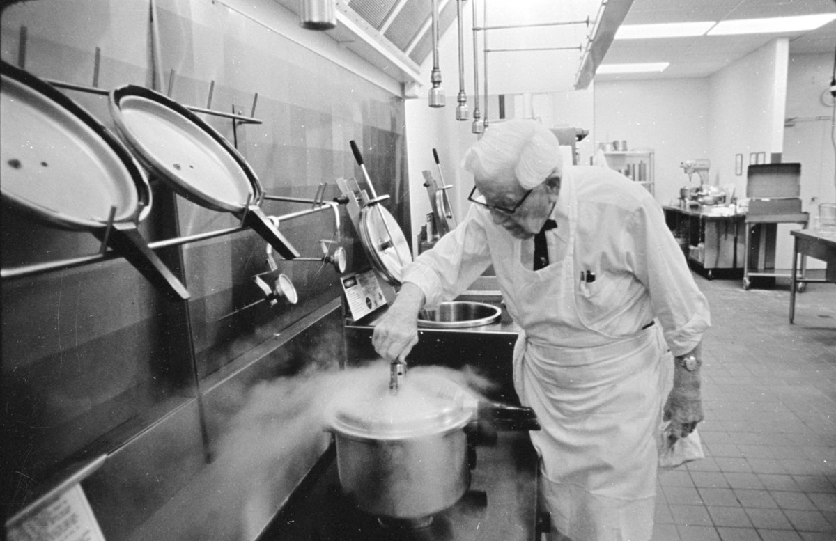 Colonel Sanders hard at work in the kitchen wearing his signature black ribbon tie underneath his apron (circa 1970).