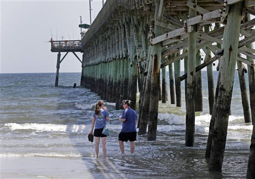 Doug Baucom, right, of Wadesboro, talks with his daughter Katie Reynolds, left, of Boone, N.C., as they stand in the surf by