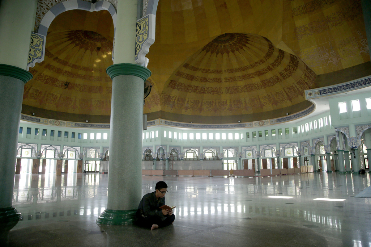 A Muslim man reads the Quran during the first day of the fasting month of Ramadan at a Mosque on the outskirts of Jakarta, In