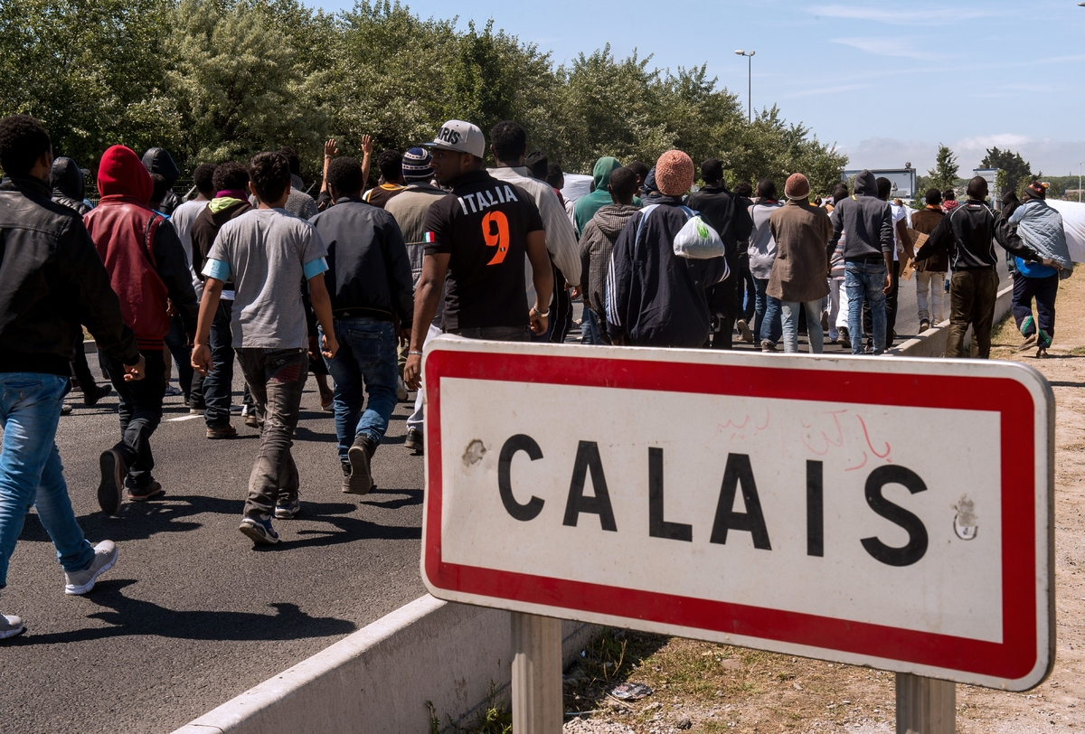 Migrants walk on June 17, 2015 towards the ferry port of Calais, northern France. Around 3,000 migrants built makeshift shelt