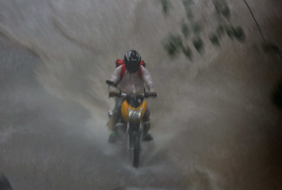 A man drives his bike through a flooded street during rain in Mumbai, India, Friday, June 19, 2015. Heavy rains in the countr