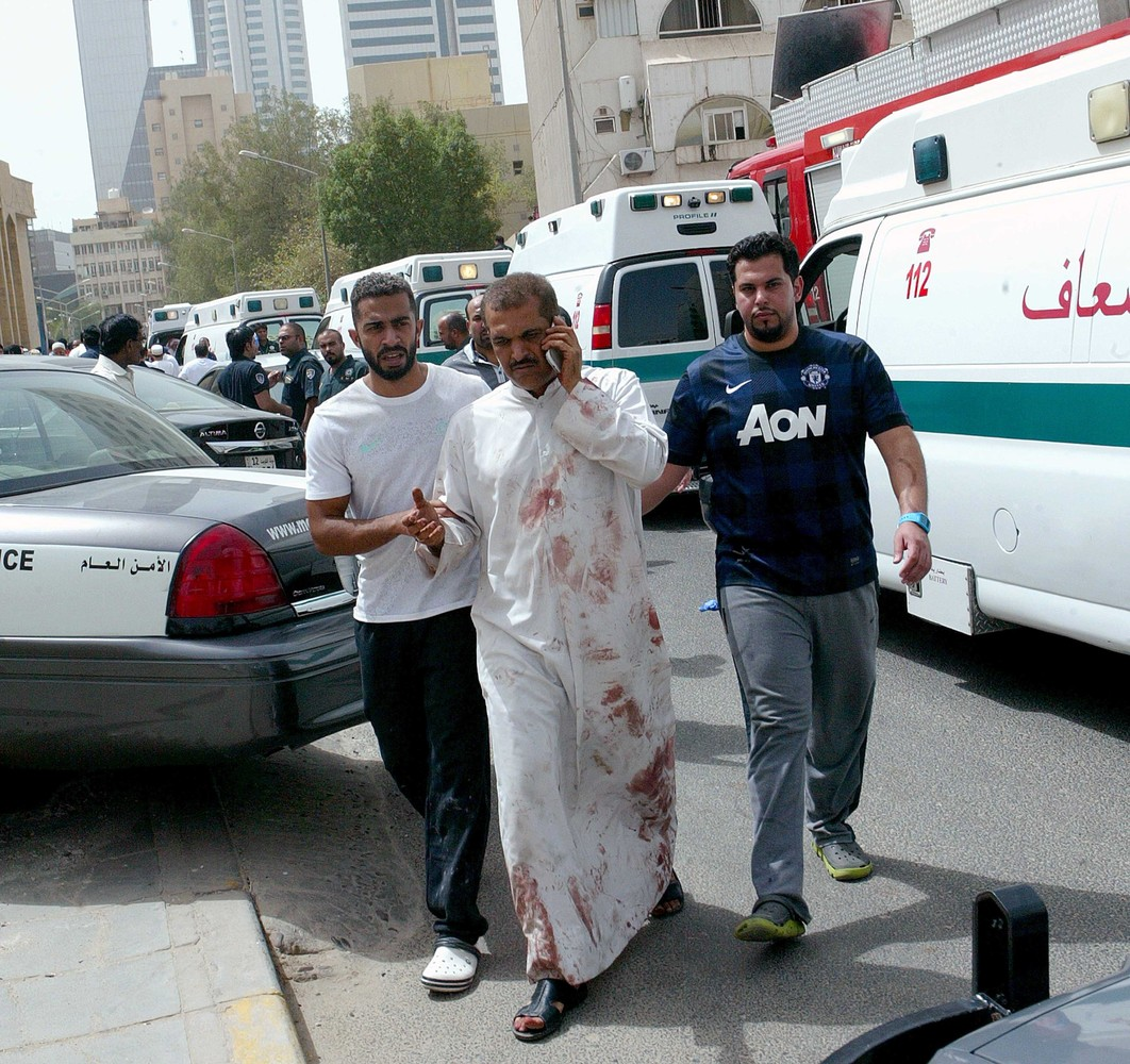 Kuwaiti men accompany a man with blood-stained clothes at the site of a suicide bombing that targeted the Shiite Al-Imam al-S