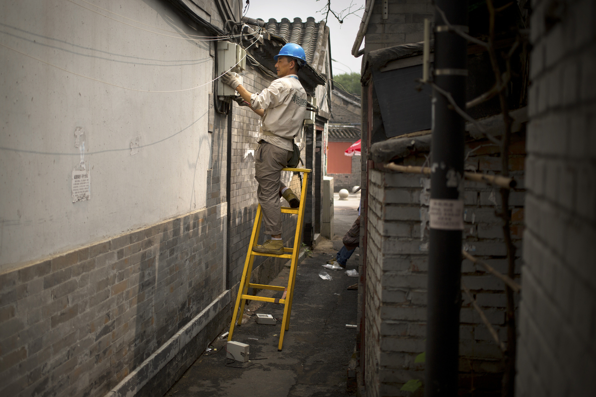 A utility worker changes electricity meters in an alleyway of a hutong, or traditional neighborhood in Beijing, China, on Jun