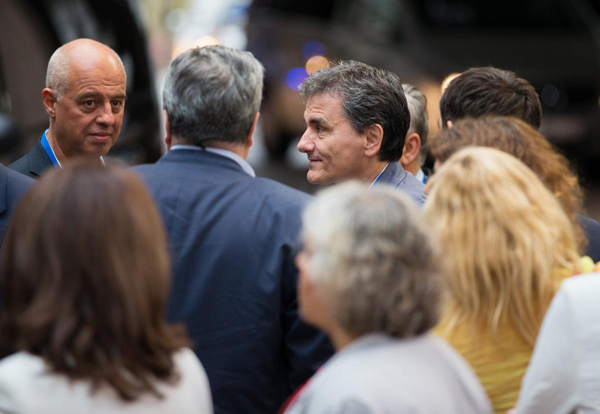 Euclid Tsakalotos, Greece's finance minister, center right, departs following all-night bailout talks in Brussels, Belgium, o