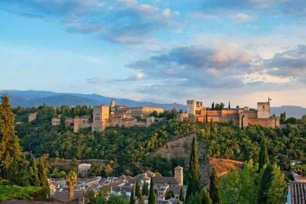 Con sus paredes rojas escarpadas contra un fondo de montañas, el complejo del palacio que domina el horizonte de Granada es q