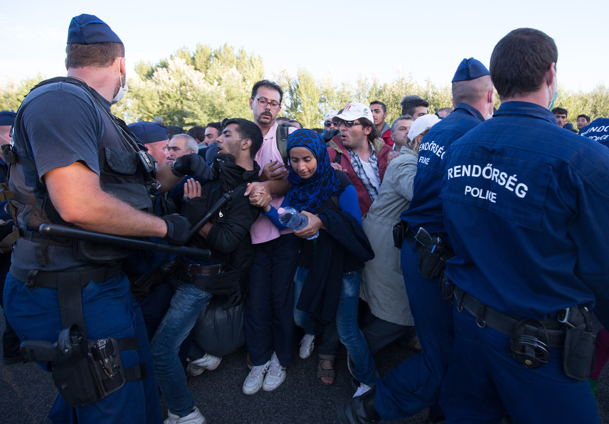 BUDAPEST, HUNGARY - SEPTEMBER 07:  Police try to hold back migrants who have refused to travel to the Roszke registration cen