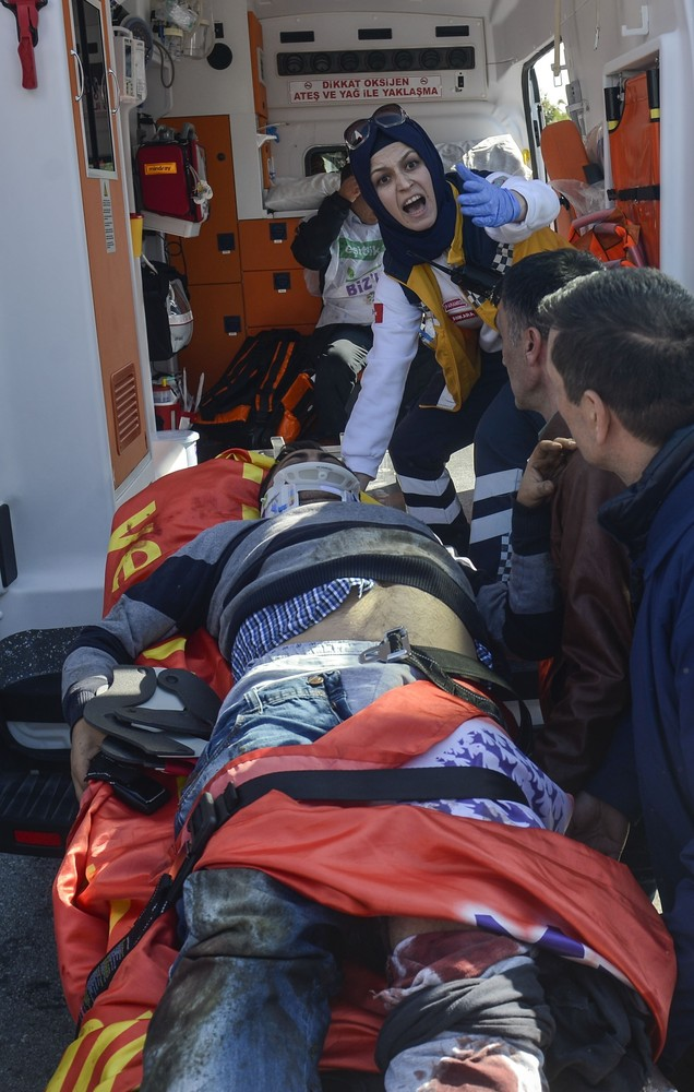A wounded man is carried into an ambulance following an explosion close to Ankara's main train station on October 10, 2015 in
