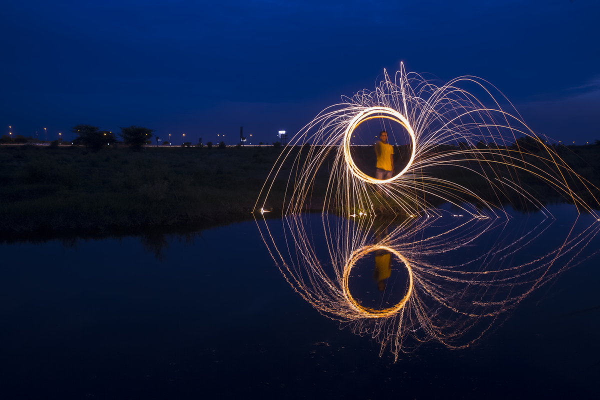 Diwali fire crackers burnt by the side of a lake which casts a crystal clear reflection.