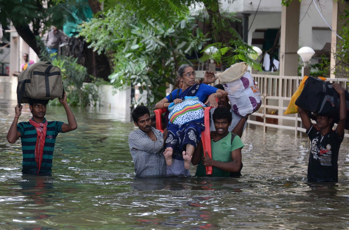Indian men carry an elderly woman on a flooded street following heavy rains in Chennai on 16 November, 2015.