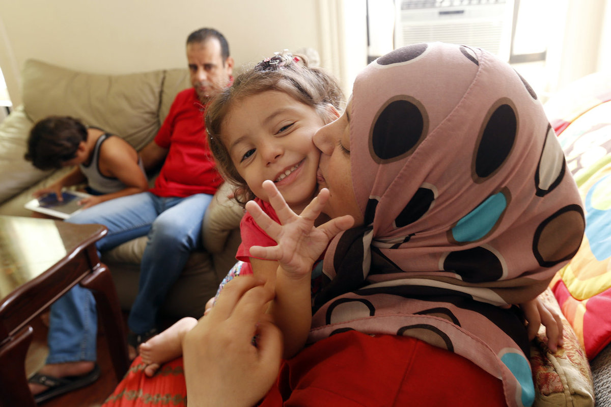 Maaesa Alroustom, center, is kissed by her mother, Suha, as her father, Hussam, back, sits with her brother Wesam in their ap