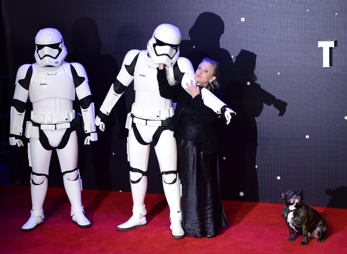 US actress Carrie Fisher (R) poses with a storm trooper as she attends the opening of the European Premiere of 'Star Wars: Th