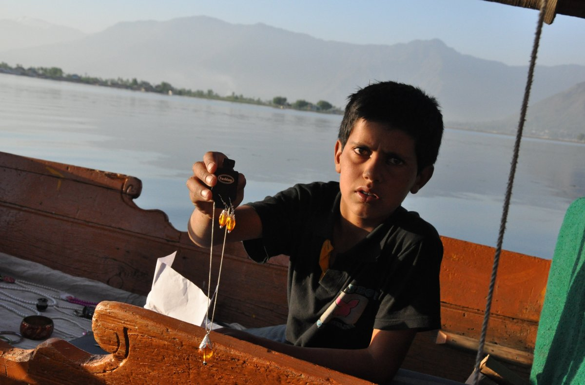 Children sell trinkets on Dal Lake.