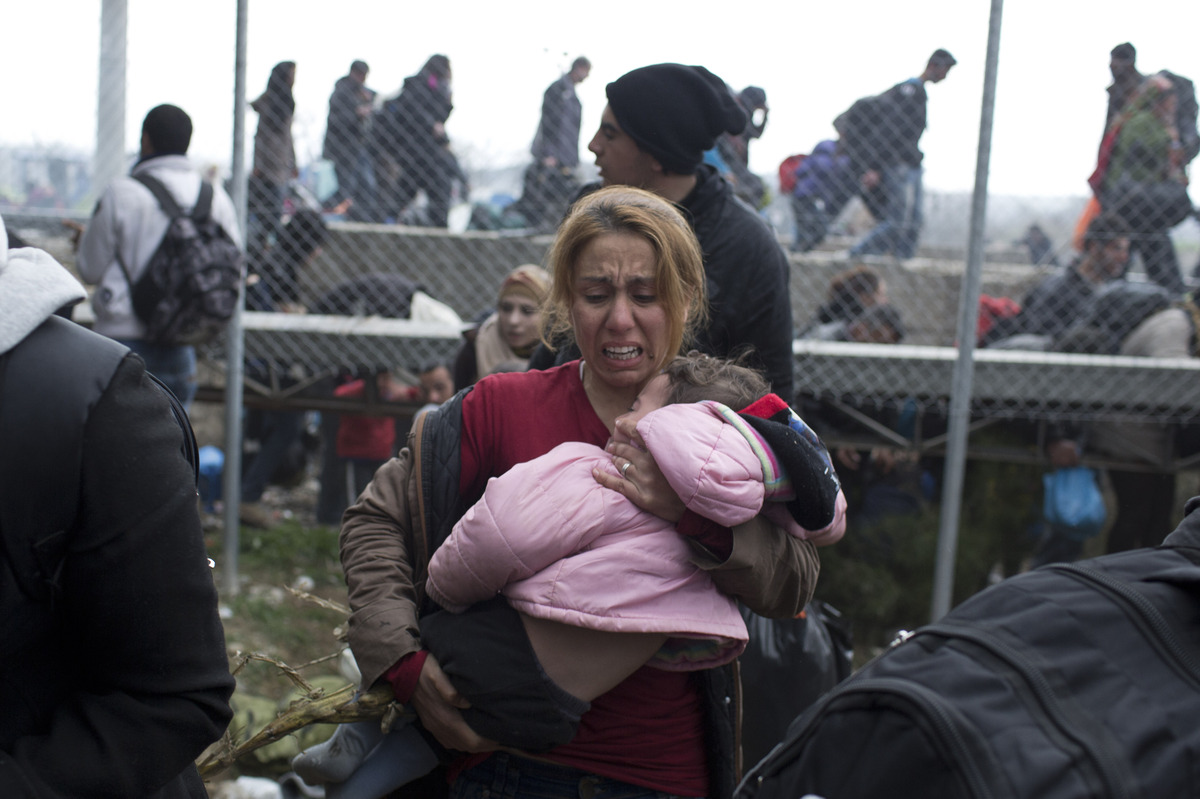A woman carries a child on the Greek side of the border as they run away after Macedonian police fired tear gas at a group of