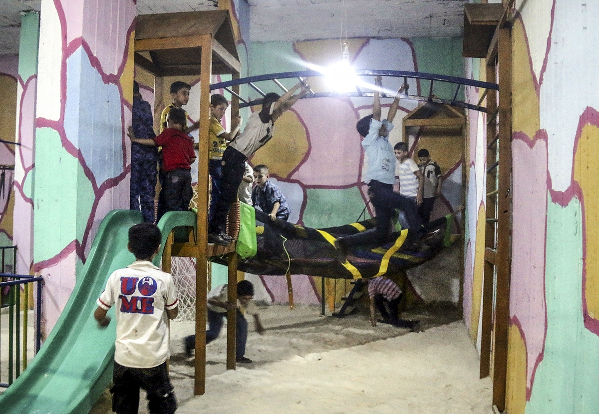 Syrian kids having fun at the subterranean playground, which constructed by activists for kids in order not to be affected bo