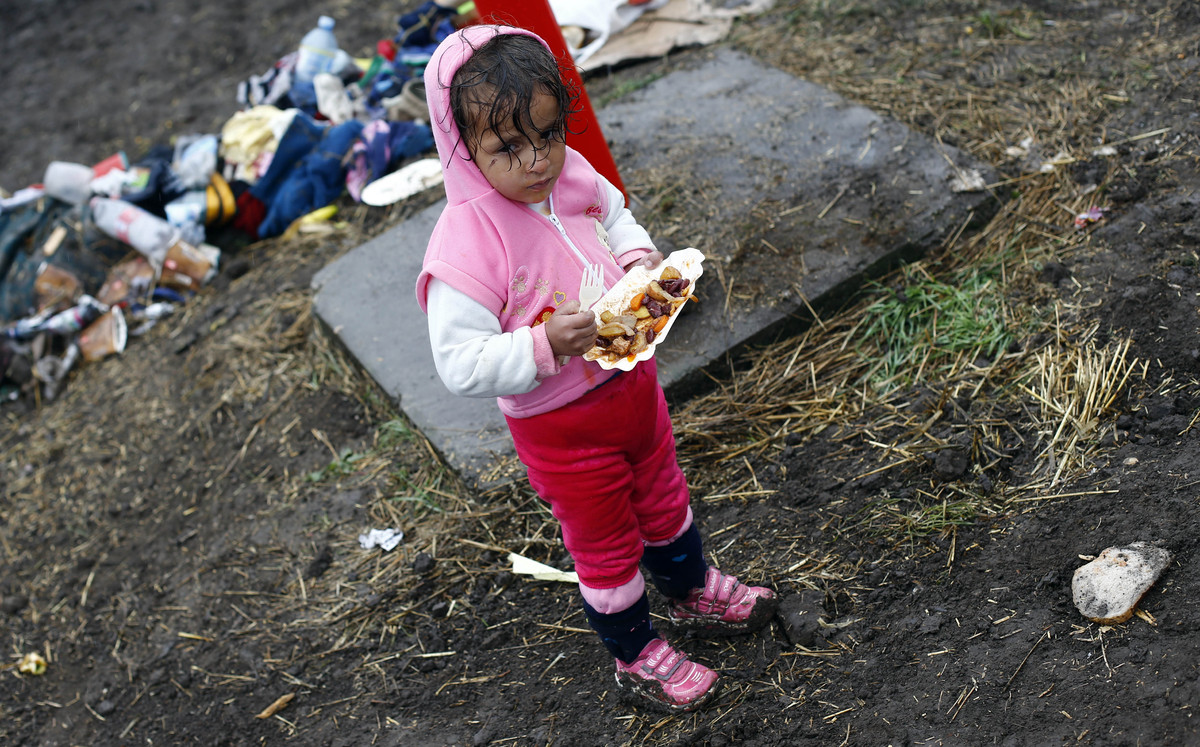 A young girl stands with her lunch in the rain at a temporary holding center for migrants near the border line between Serbia