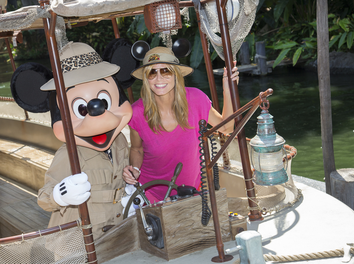 This image released by Disneyland shows TV personality and model Heidi Klum posing with Mickey Mouse aboard the Jungle Cruise