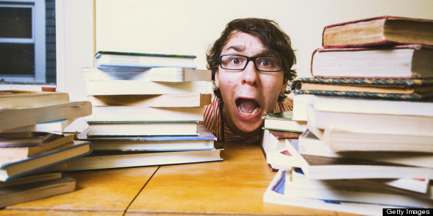 A stressed out college or high school student hiding behind piles of books on top of his desk. He is wearing glasses, and has brown hair.