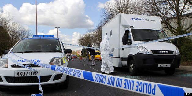 Forensic police officers examine evidence at the crime scene where two men escaped from a prison van that came under attack on Regent Road in Salford.
