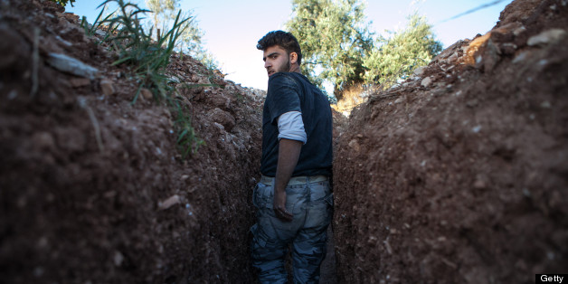 A Syrian rebel fighter throughout a trench dig by the rebels to hold a position, 100m far from the regime-controlled military base of Wadi Deif on June 14, 2013 in the village of Kfarruma in the Syrian province of Idlib.   AFP PHOTO DANIEL LEAL-OLIVAS        (Photo credit should read DANIEL LEAL OLIVAS/AFP/Getty Images)