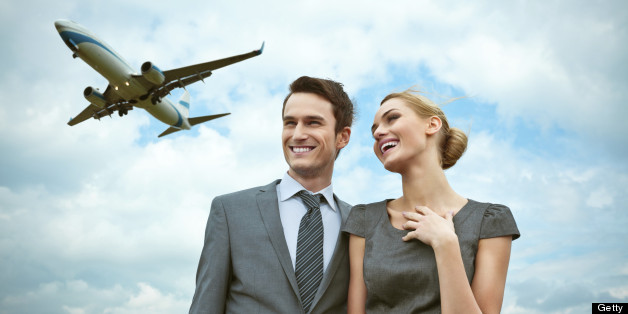 Outdoor portrait of business couple with flying airplane in the background.