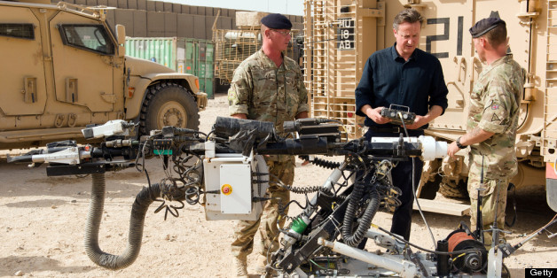 CAMP BASTION, AFGHANISTAN - JUNE 29:  British Prime Minister David Cameron (C) is shown a remote-controlled IED detection unit used in regional operations during a visit to Camp Bastion on June 29, 2013 near Lashkar Gah, in the southern Helmand province, Afghanistan. Cameron made an unannounced visit to Afghanistan visiting troops in Helmand as the NATO military coalition hands responsibility over to local forces.  (Photo by Leon Neal - WPA Pool/Getty Images)