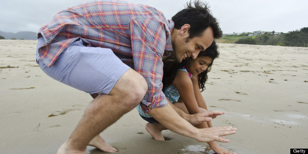 Loving Hispanic father with his daughter on the beach