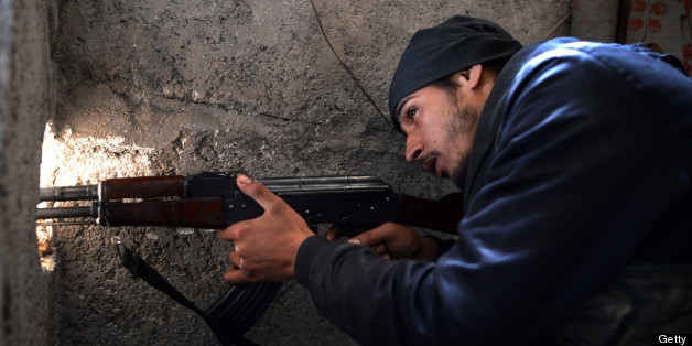 A Syrian rebel fighter points his weapon towards the positions of Syrian government forces in the Saladin district of the northern Syrian city of Aleppo on April 8, 2013.     AFP PHOTO / DIMITAR DILKOFF        (Photo credit should read DIMITAR DILKOFF/AFP/Getty Images)