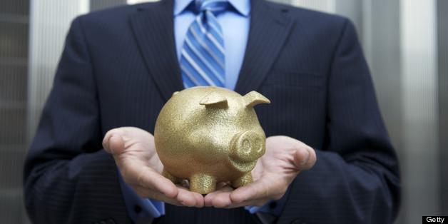 Businessman stands holding a golden piggy bank cradled in his hands
