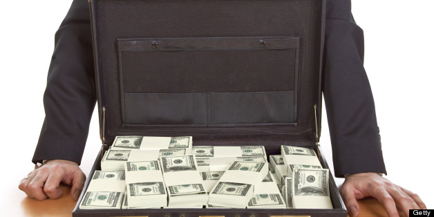 Business man standing next to open briefcase with money ,bribe concept