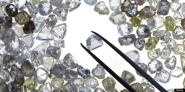 An uncut diamond is selected from a collection of colorless and colored diamonds on a sorting table at DTC Botswana, a unit of De Beers, in Gaborone, Botswana, on Thursday, Oct. 25, 2012.De Beers, the biggest diamond producer by revenue, is moving the sorting and trading of rough stones to Botswana from London to secure access to the world's largest supplier of diamonds by value and challenge Antwerp's dominance as the world's biggest trading hub for rough diamonds. Photographer: Chris Ratcliffe/Bloomberg via Getty Images