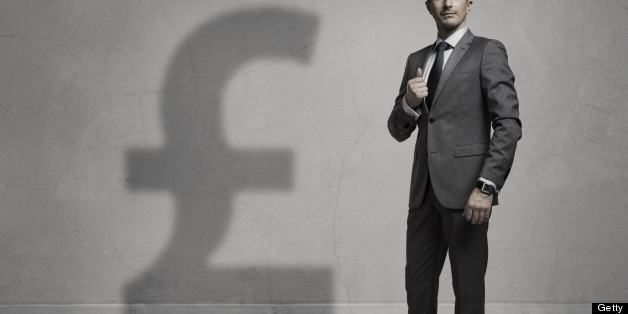 Businessman with a big Pound Sterling shadow. Success concept. Grain is added.