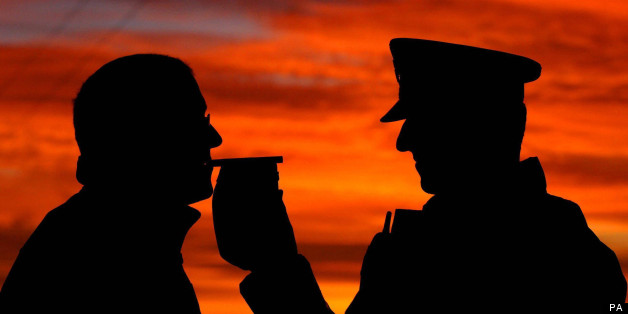 A motorist stopped by police taking a breath test