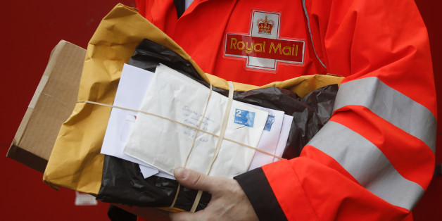 A Royal Mail Group Ltd. employee carries a bundle of letters during his delivery round in London, U.K. on Thursday, May 30, 2013. The U.K. government appointed UBS AG and Goldman Sachs Group Inc. as joint global coordinators and joint bookrunners for the sale of Royal Mail Group Ltd., the state-owned postal service. Photographer: Simon Dawson/Bloomberg via Getty Images