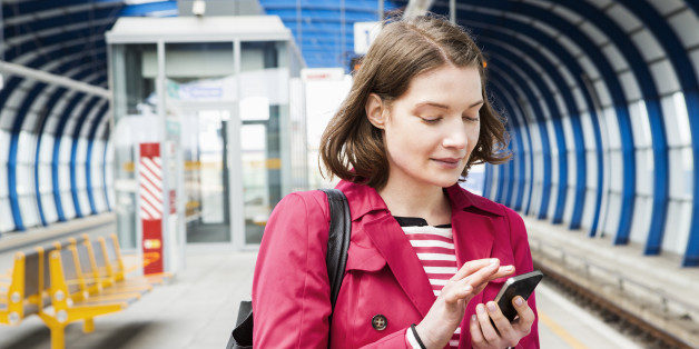 Woman texting while waiting for train.