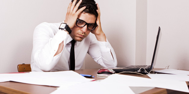 Young businessman holding his head and seems so worried