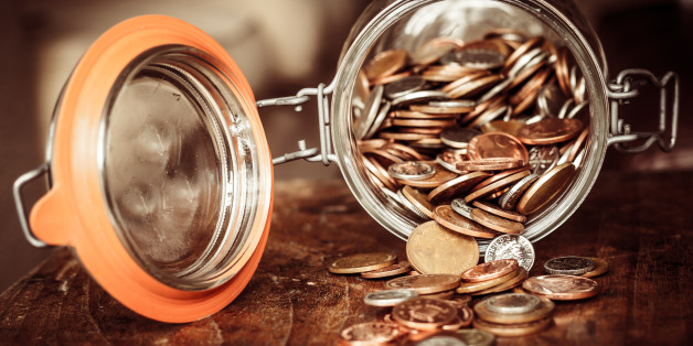 A jar of sterling coins is tipped on its side with the coins spilling out on to a wooden surface. The jar denotes a savings pot.