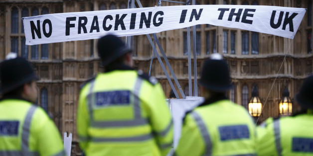 British police secure the area where demonstrators erected a mock fracking rig with a banner reading 'No fracking in the UK' in a protest against hydraulic fracturing for shale gas outside the Houses of Parliament in London on December 1, 2012. The demonstration organised by various groups protested against any expansion into Britain of the pratcice of 'hydraulic fracturing' or 'fracking' for shale gas which the Campaign Against Climate Change group, one of the organisations involved in the acti