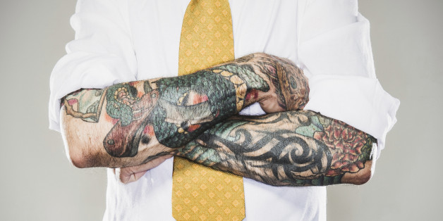 A business man stands with his tattooed arms folded across his white collared shirt and tie.  Two forearm sleeve tattoos.  (Getty)