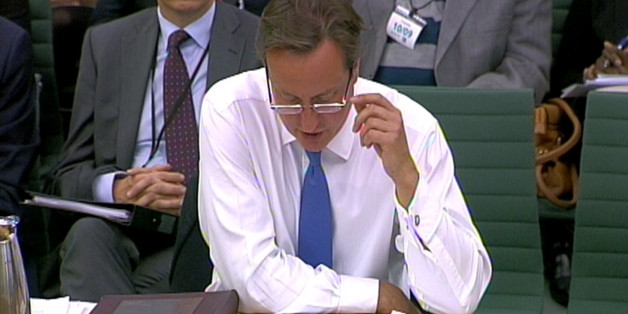 Prime Minister David Cameron wearing glasses answers questions in front of Liaison Select Committee