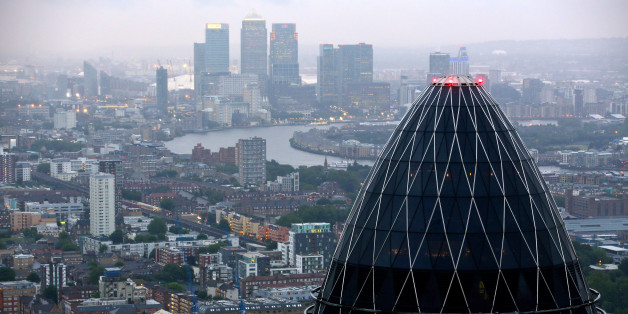 The Swiss Re Insurance building, also known as 'the Gherkin', foreground, and the towers of the Canary Wharf business district are seen against the city skyline in London, U.K. on Thursday, July 12, 2012. Banks being probed for attempting to rig benchmark interest rates could face $6 billion of related litigation costs, analysts at Morgan Stanley estimated. Photographer: Jason Alden/Bloomberg via Getty Images