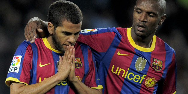 Barcelona's Brazilian defender Daniel Alves (L) is congratuled by his teammate French defender Eric Abidal (R) after scoring during a Spanish League football match against Sevilla at the Camp Nou Stadium in Barcelona , on October 30, 2010. AFP PHOTO / JOSEP LAGO (Photo credit should read JOSEP LAGO/AFP/Getty Images)