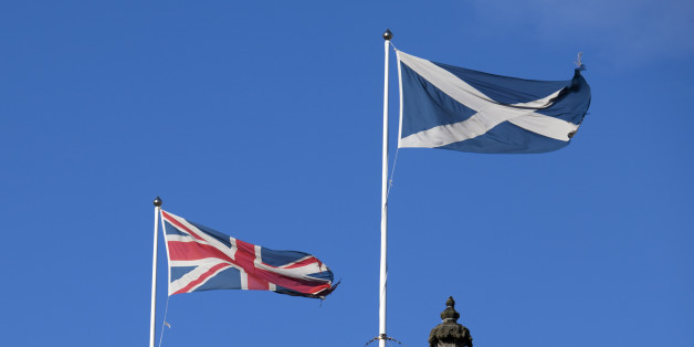 Scottish Flag (the Saltire or Cross of St. Andrew) and the British flag (the Union Jack) blowing together against a blue sky.